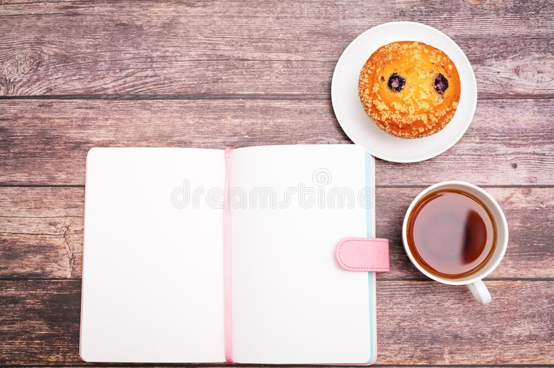 Monday Morning Concept, Hot tea and muffin cake on wooden workspace stock image