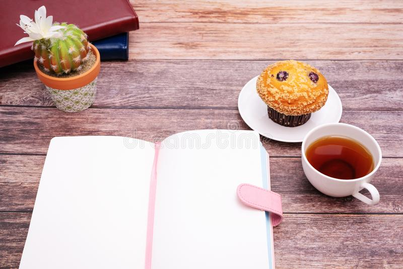 Monday Morning Concept, Hot tea and muffin cake on wooden workspace stock photo