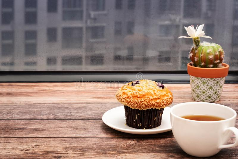 Monday Morning Concept, Hot tea and muffin cake on wooden workspace stock images