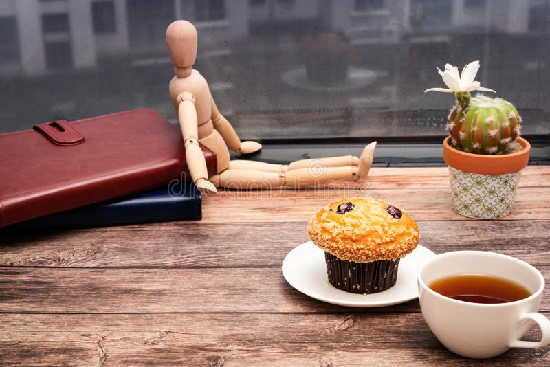 Monday Morning Concept, Hot tea and muffin cake on wooden workspace stock photography