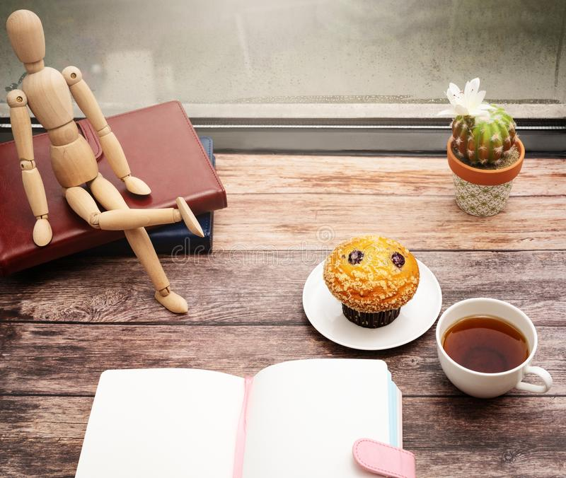 Monday Morning Concept, Hot tea and muffin cake on wooden workspace near window royalty free stock photos