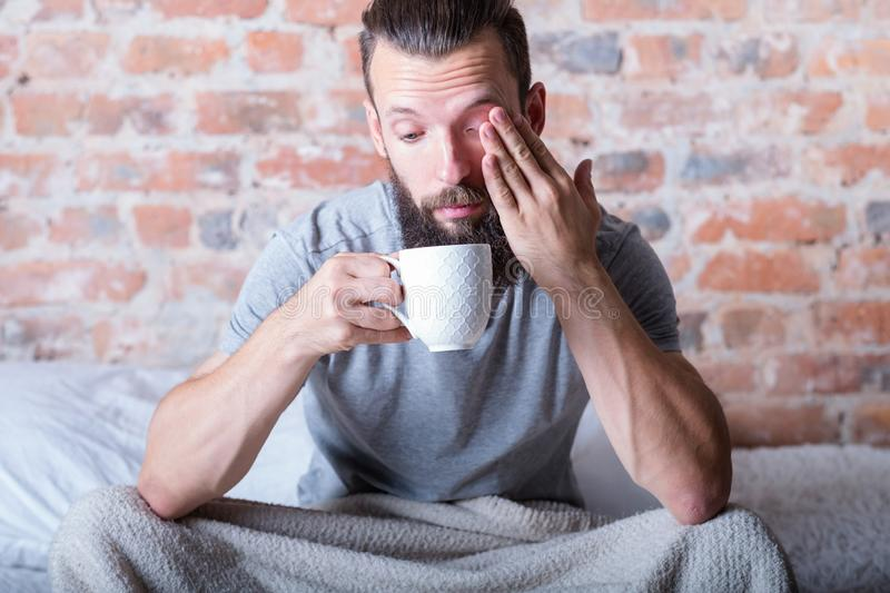 Monday morning drowsiness man bed cup distracted. Monday morning again. Drowsiness. Man sitting in bed with cup of hot drink in hand. Rubbing eye, looking stock photos