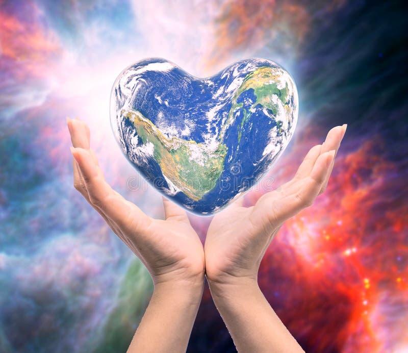 Monde dans la forme de coeur avec les mains finies d'humain de femmes photographie stock