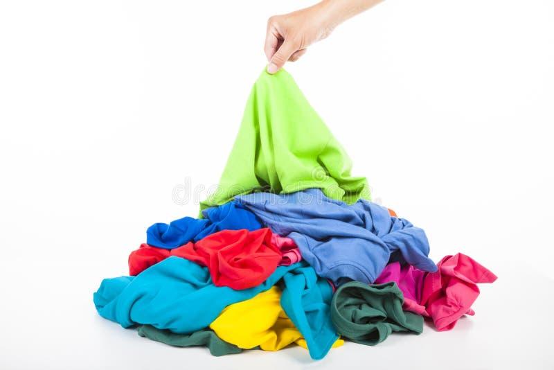 Monde a mano encima de la camisa en la pila de ropa imagenes de archivo