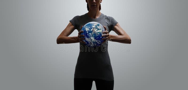 Mondo adatto autorizzato della tenuta della donna in sue mani fotografia stock libera da diritti
