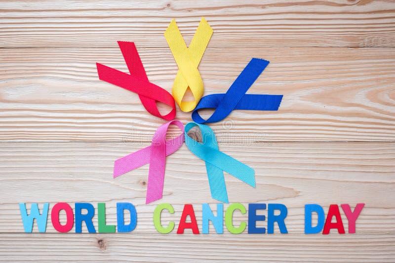 Mondo cancro giorno 4 febbraio nastri variopinti di consapevolezza; blu, rosso, rosa e colore giallo su fondo di legno per sosten fotografia stock libera da diritti
