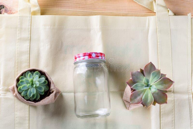 Mondo esente da plastica Prodotto-borsa verde fatta da bambù o da riutilizzazione, succulente e barattolo di vetro sul fondo di l fotografia stock