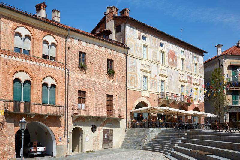 Ancient buildings with red bricks and frescos in a sunny day, upper city square in Mondovi, Italy. MONDOVI, ITALY - AUGUST 18, 2016: Ancient buildings with red royalty free stock photo