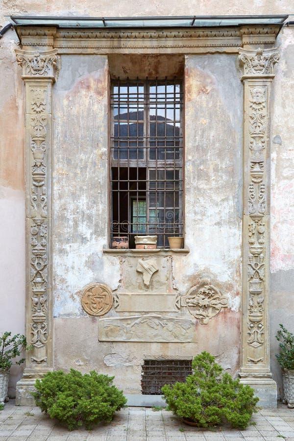 MONDOVI, ITALY - AUGUST 16, 2016: Ancient facade with columns, bas relief and capital in summer in Mondovi, Italy. MONDOVI, ITALY - AUGUST 16, 2016: Ancient royalty free stock photos