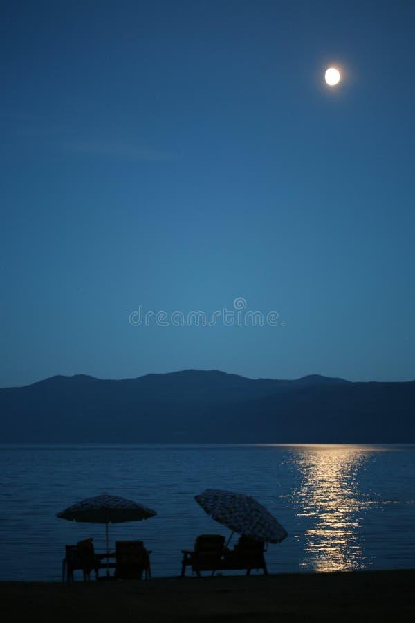 Mondschein auf Wasser durch Strand. stockfotos