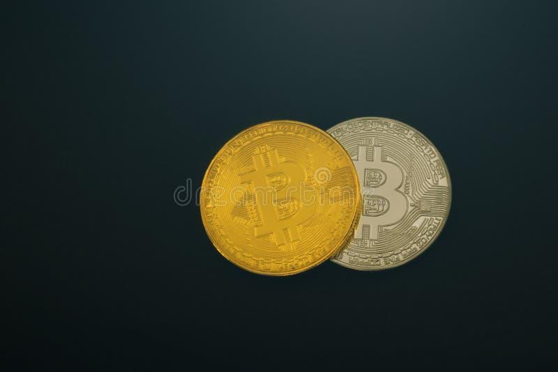 Moneda Bitcoin de la plata y de oro en un fondo negro aislante fotografía de archivo