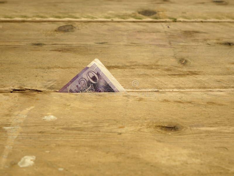 Moneda británica exprimida entre las líneas fotografía de archivo