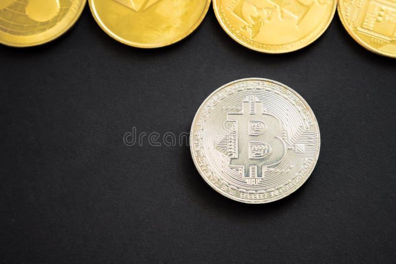 Moneda crypto de la moneda del bitcoin de plata al lado de otras: Litecoin, ondulaci?n, Monerd, moneda de Ethereum en fondo negro fotografía de archivo