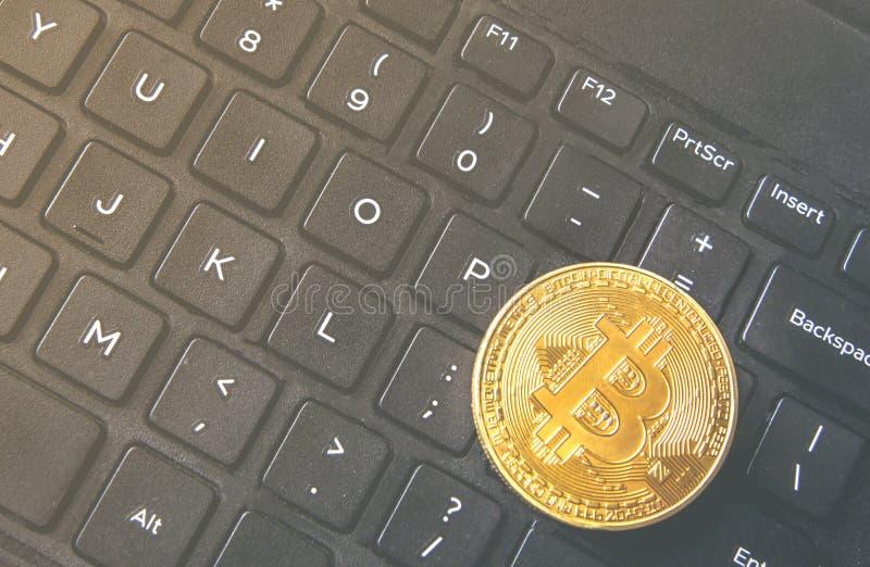Moneda de Bitcoin colocada en el teclado negro moderno del cuaderno Valor virtual del intercambio del primer, dinero digital cryp fotografía de archivo