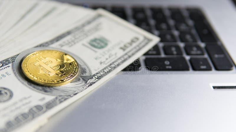 Moneda de Bitcoin con el ordenador portátil y dólar Monedas de oro de Bitcoin en billetes de banco y el ordenador portátil de un  foto de archivo