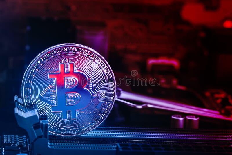 Moneda de Bitcoin con resplandor rojo abstracto en el fondo de la placa madre y de las luces azules rojas Símbolo de la moneda cr imágenes de archivo libres de regalías