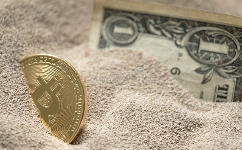 Moneda de Bitcoin vista enterrada parcialmente en arena del silicio así como un billete de banco de un dólar imágenes de archivo libres de regalías