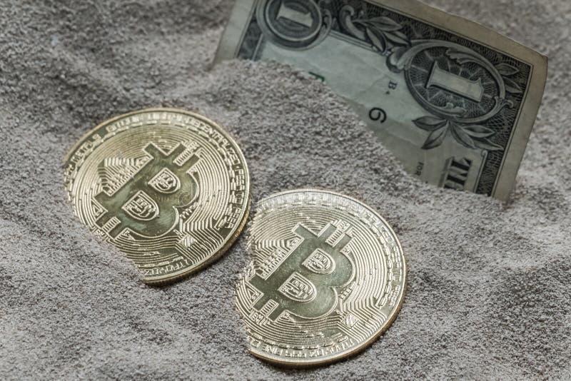 Moneda de Bitcoin vista enterrada parcialmente en arena del silicio así como un billete de banco de un dólar fotografía de archivo libre de regalías
