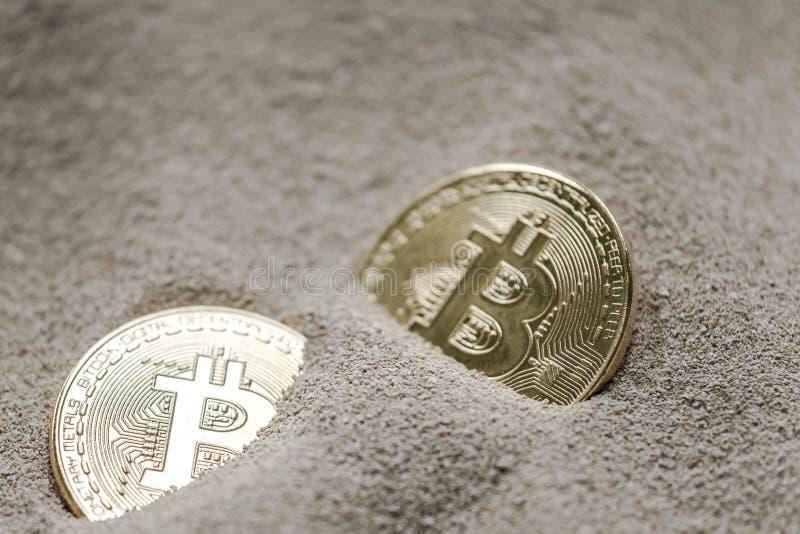 Moneda de Bitcoin vista enterrada parcialmente en arena del silicio así como un billete de banco de un dólar imagen de archivo libre de regalías