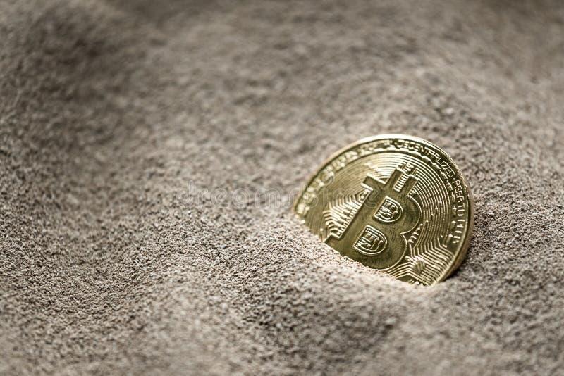 Moneda de Bitcoin vista enterrada parcialmente en arena del silicio así como un billete de banco de un dólar imagen de archivo