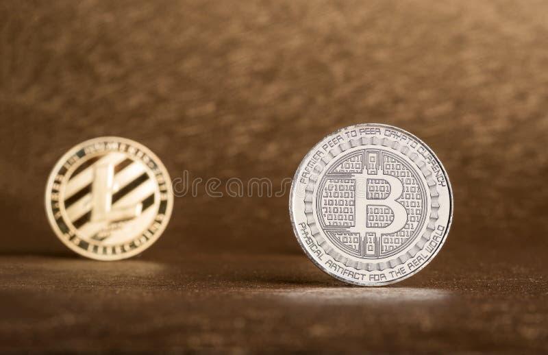 Moneda de Cryptocurrency Lite, Bitcoin de plata en backgrou áspero de oro imagenes de archivo