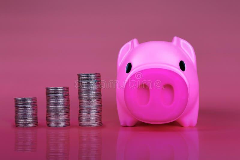 Moneda de la reserva de la hucha del rosa en el fondo rosado, banco rosado guarro con las monedas del crecimiento que significa c imagenes de archivo