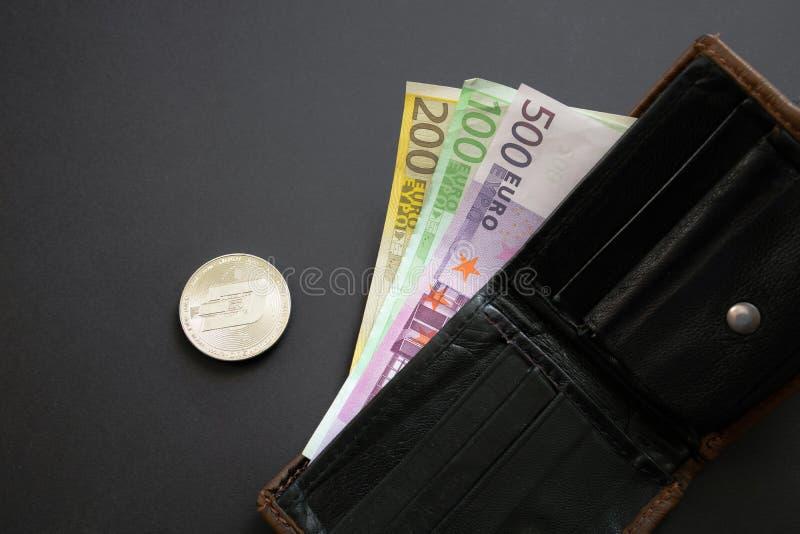 Moneda de la rociada al lado de los billetes de banco euro que se pegan fuera de una cartera en fondo negro Moneda de Digitaces,  imagenes de archivo
