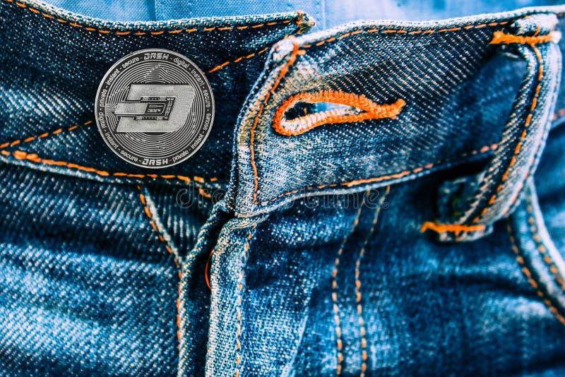 Moneda de la rociada en vez de los botones en vaqueros imagen de archivo