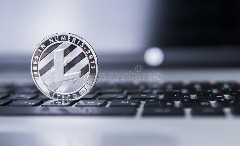 Moneda de Litecoin en un ordenador portátil Moneda crypto de Litecoins en un teclado del negro del ordenador portátil Moneda de D fotos de archivo libres de regalías