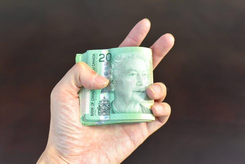 Moneda de los dólares canadienses de la tenencia de la mano fotos de archivo libres de regalías