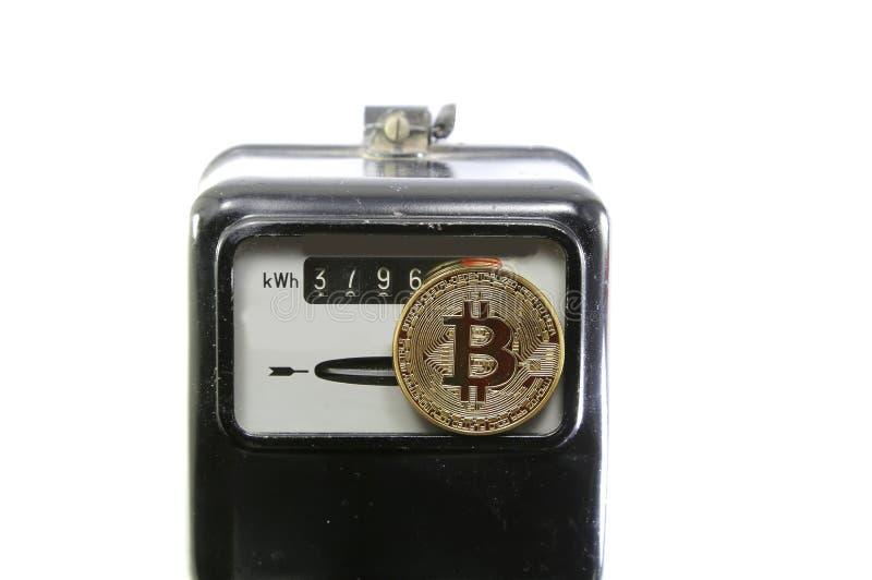 Moneda de oro de BitCoin sobre un metro análogo de la energía eléctrica fotos de archivo libres de regalías
