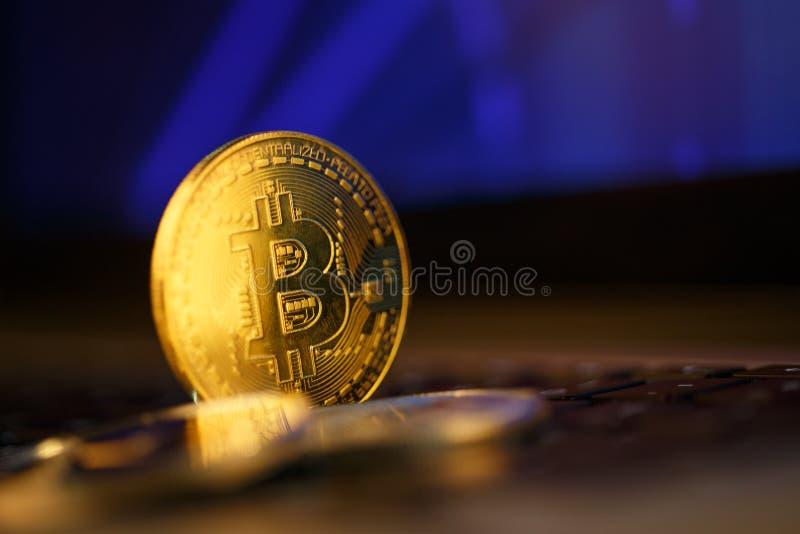 Moneda de oro de Bitcoin y fondo defocused de la carta imágenes de archivo libres de regalías