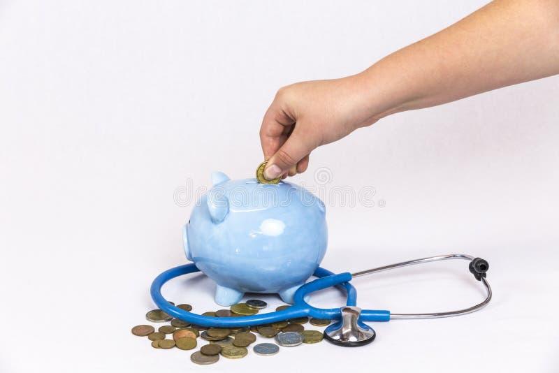 Moneda de oro de caída de la chica joven en la hucha azul fotografía de archivo libre de regalías