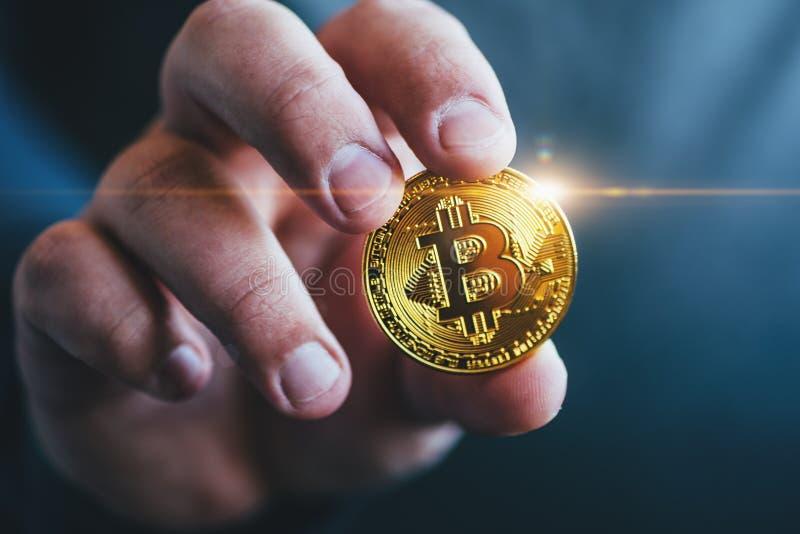 Moneda de oro del bitcoin de Cryptocurrency en la mano del hombre - símbolo de la moneda crypto - dinero virtual electrónico fotografía de archivo libre de regalías
