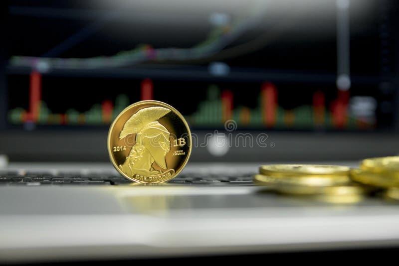 Moneda de oro del bitcoin del titán con las monedas de oro que mienten alrededor en un teclado de plata del gráfico de la carta d fotos de archivo libres de regalías