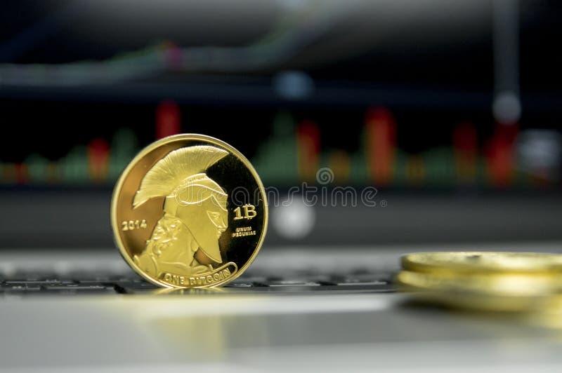 Moneda de oro del bitcoin del titán con las monedas de oro que mienten alrededor en un teclado de plata del gráfico de la carta d foto de archivo libre de regalías