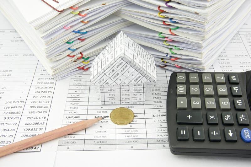 Moneda de oro delante de la casa con el lápiz y la calculadora imagen de archivo libre de regalías