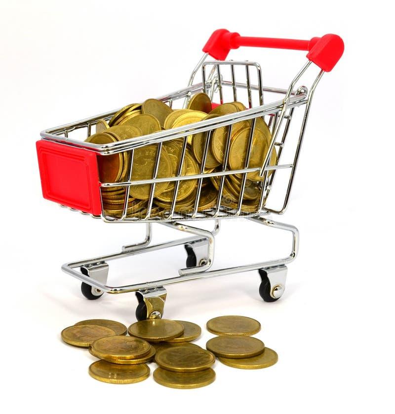 Moneda de oro en carro de la compra en el fondo blanco fotos de archivo