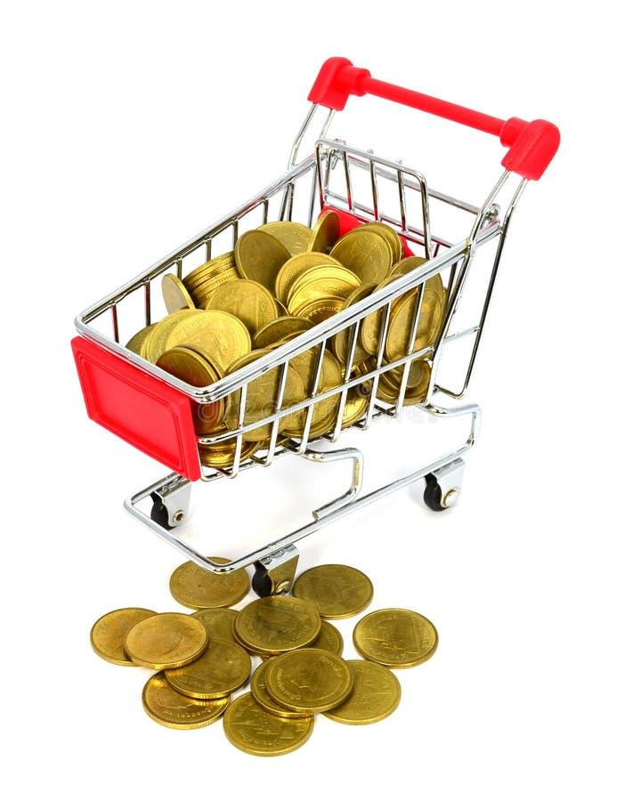 Moneda de oro en carro de la compra en el fondo blanco imagen de archivo