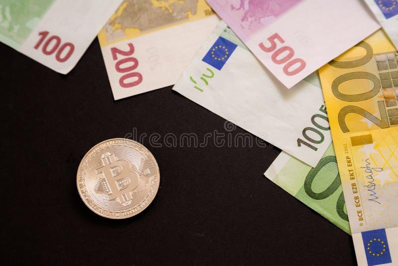 Moneda de plata de Bitcoin al lado de billetes de banco euro en fondo negro Moneda de Digitaces, mercado de la cadena de bloque C fotografía de archivo libre de regalías