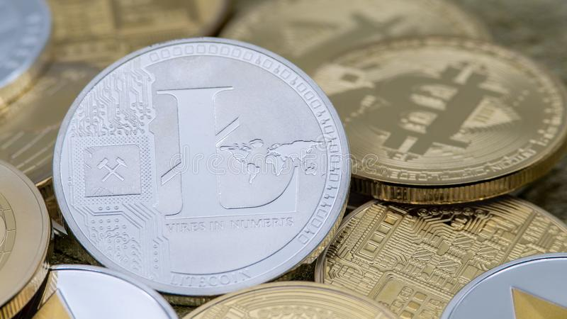 Moneda de plata de Litecoin del metal físico sobre otras monedas Cryptocurrency imagenes de archivo