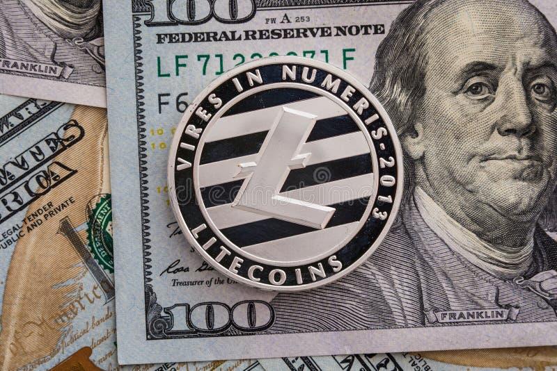 Moneda de plata de Litecoin en fondo de los billetes de banco de los dólares Concepto del negocio y de la tecnología Litecoin fís imagen de archivo libre de regalías
