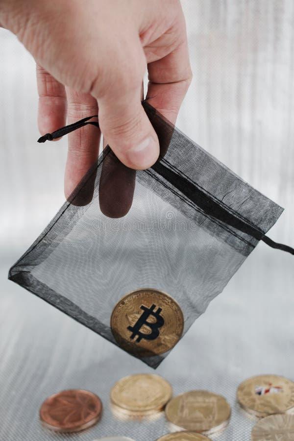 Moneda del bitcoin del oro en bolso negro fotografía de archivo