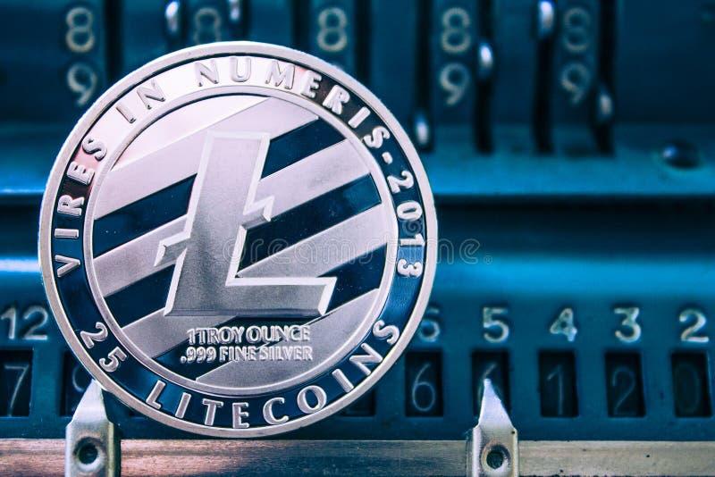 Moneda del litecoin en el fondo de la máquina sumadora de los números imagen de archivo libre de regalías