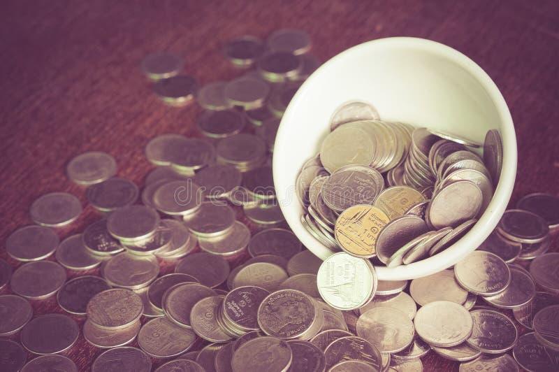 Moneda en la taza foto de archivo