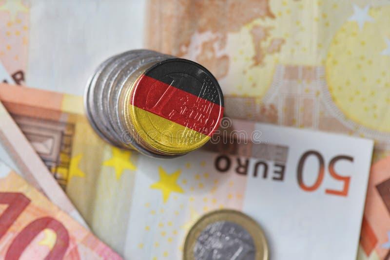 Moneda euro con la bandera nacional de Alemania en el fondo euro de los billetes de banco del dinero imagenes de archivo