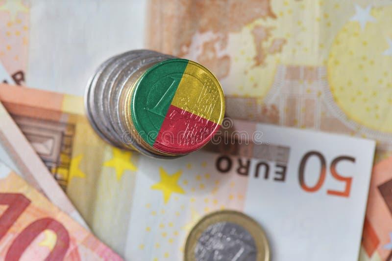 Moneda euro con la bandera nacional de Benin en el fondo euro de los billetes de banco del dinero imagen de archivo libre de regalías
