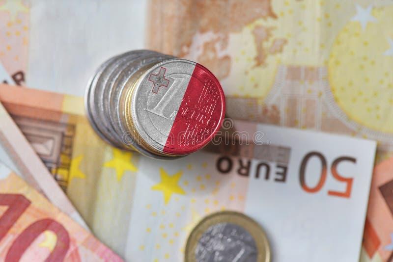Moneda euro con la bandera nacional de Malta en el fondo euro de los billetes de banco del dinero fotografía de archivo libre de regalías