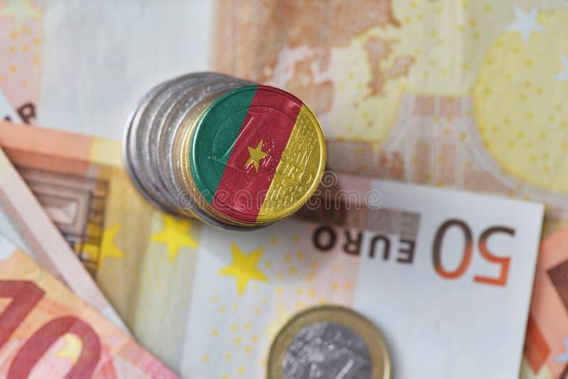 Moneda euro con la bandera nacional del Camerún en el fondo euro de los billetes de banco del dinero imagen de archivo libre de regalías