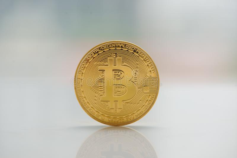 Moneda física del bitcoin del oro de la moneda de Digitaces en la tabla cerca de los wi fotografía de archivo libre de regalías